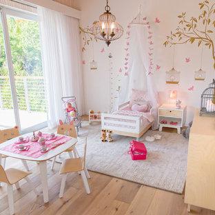 Imagen de habitación de bebé niña costera, grande, con paredes beige, suelo de madera clara y suelo beige
