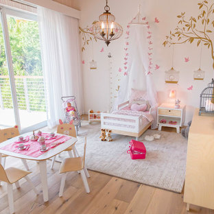 Photo of a large nautical nursery for girls in Miami with beige walls, light hardwood flooring and beige floors.