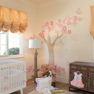 Photo of a large mediterranean nursery for girls in Los Angeles with white walls and medium hardwood flooring.