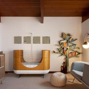 Diseño de habitación de bebé neutra retro, de tamaño medio, con paredes blancas, moqueta y suelo beige