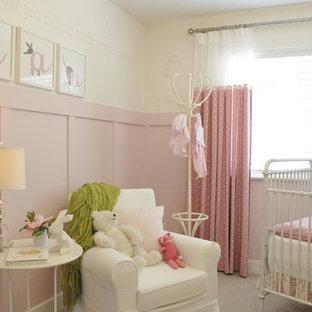 Diseño de habitación de bebé niña tradicional, de tamaño medio, con paredes rosas, moqueta y suelo gris