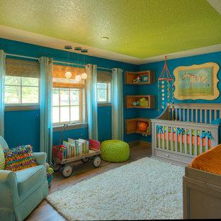 Large eclectic gender neutral nursery in Portland with blue walls, medium hardwood flooring and brown floors.