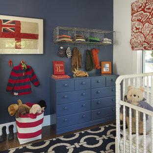 Ejemplo de habitación de bebé niño clásica con paredes azules y suelo de madera oscura