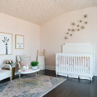 Example of a transitional girl dark wood floor and brown floor nursery design in Chicago with pink walls