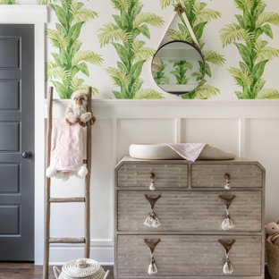 Design ideas for a traditional nursery for girls in Charlotte with white walls, medium hardwood flooring and brown floors.