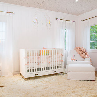 Cette image montre une chambre de bébé vintage de taille moyenne avec un mur blanc, un sol en bois clair et un sol jaune.