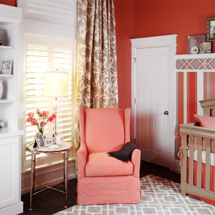 This is an example of a medium sized traditional nursery for girls in Other with orange walls and medium hardwood flooring.