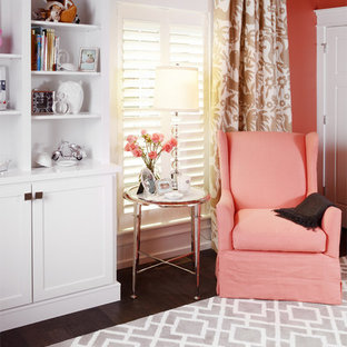 Medium sized traditional nursery for girls in Other with orange walls and medium hardwood flooring.