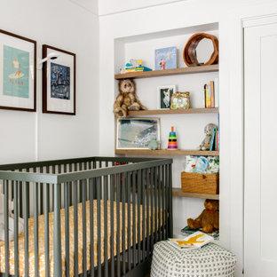 Foto di una cameretta per neonati stile marinaro con pareti bianche, pavimento in legno massello medio, pavimento marrone, travi a vista e soffitto in perlinato