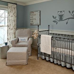 Imagen de habitación de bebé neutra tradicional con paredes azules y moqueta