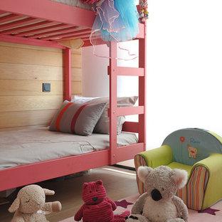 Modelo de habitación de bebé niña actual, pequeña, con paredes beige, suelo de madera clara y suelo beige
