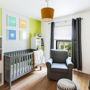 Ispirazione per una cameretta per neonati neutra moderna con pareti verdi e parquet chiaro