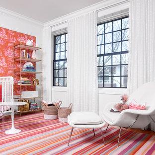 Exemple d'une chambre de bébé chic avec un mur blanc, un sol en bois brun et un sol rose.