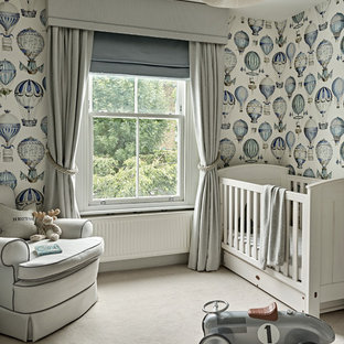 Photo of a mid-sized transitional nursery for boys in London with carpet, multi-coloured walls and beige floor.