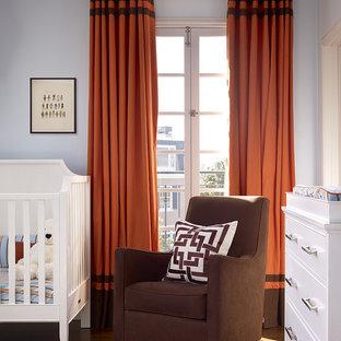 Cette photo montre une chambre de bébé neutre chic avec un mur bleu et un sol en bois brun.