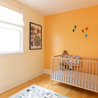 Idée de décoration pour une chambre de bébé neutre nordique avec un mur orange, un sol en bois clair et un sol jaune.