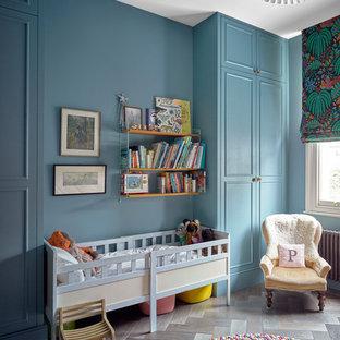 Idee per una cameretta per neonati neutra chic di medie dimensioni con pareti blu, parquet scuro e pavimento marrone
