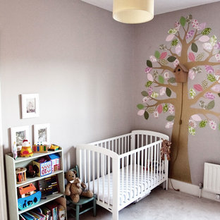 Inspiration for a mid-sized traditional nursery for girls in London with multi-coloured walls, carpet and beige floor.