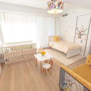 Cette image montre une chambre de bébé fille traditionnelle de taille moyenne avec un mur blanc et un sol en bois clair.