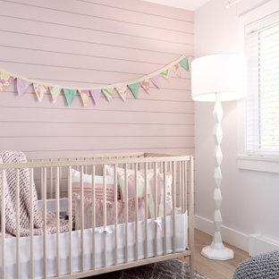 Imagen de habitación de bebé niña machihembrado, de estilo de casa de campo, de tamaño medio, con paredes rosas, suelo de madera clara, suelo beige y machihembrado