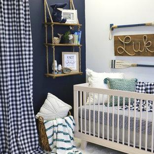 Diseño de habitación de bebé niño costera, pequeña, con paredes azules, suelo laminado y suelo beige