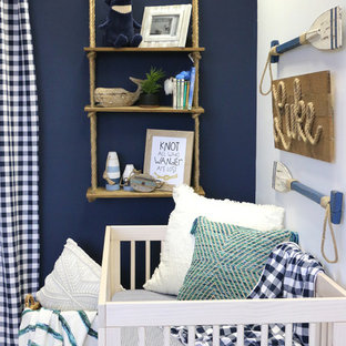 Photo of a small beach style nursery for boys in Austin with blue walls, laminate floors and beige floors.