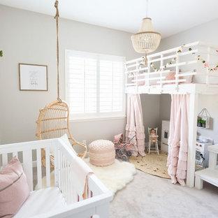 Modelo de habitación de bebé niña romántica, de tamaño medio, con paredes grises, moqueta y suelo beige