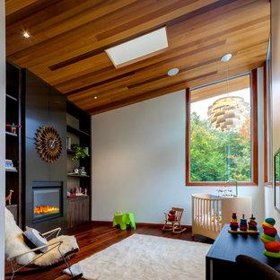 Bild på ett funkis könsneutralt babyrum, med vita väggar, mörkt trägolv och orange golv