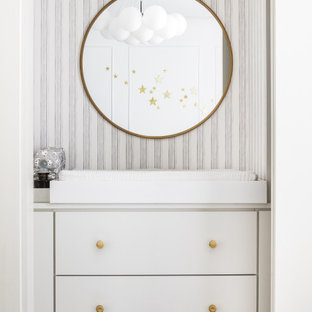 Modelo de habitación de bebé niño panelado, moderna, de tamaño medio, con paredes blancas, suelo de mármol y panelado
