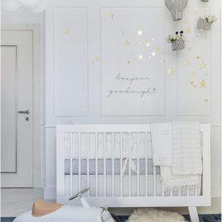 Exemple d'une chambre de bébé garçon moderne de taille moyenne avec un mur blanc, un sol en marbre et du lambris.
