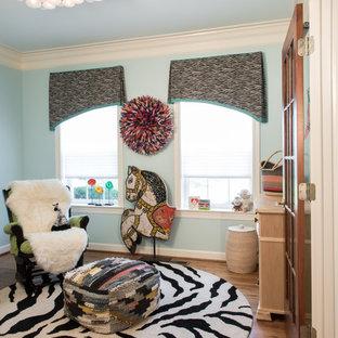 Small bohemian nursery for boys with blue walls and medium hardwood flooring.