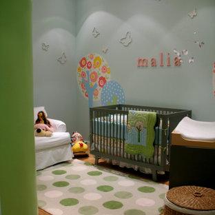 Ejemplo de habitación de bebé neutra contemporánea, pequeña, con paredes azules y suelo de madera clara