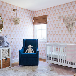 Coastal nursery for girls in Los Angeles with pink walls and light hardwood flooring.