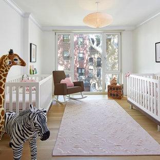 Imagen de habitación de bebé niña tradicional renovada con paredes blancas y suelo de madera clara