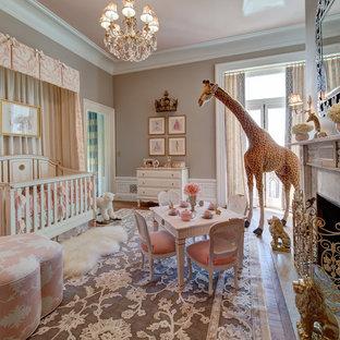Exemple d'une grand chambre de bébé fille chic avec un mur beige et un sol en bois brun.