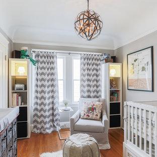 Exemple d'une chambre de bébé neutre chic de taille moyenne avec un mur gris, un sol en bois brun et un sol orange.