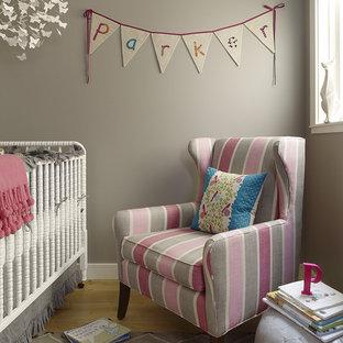 Modelo de habitación de bebé niña clásica renovada, pequeña, con paredes grises y suelo de madera clara