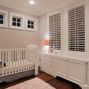 Ejemplo de habitación de bebé neutra clásica con paredes beige, suelo de madera oscura y suelo marrón