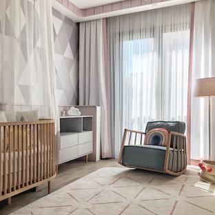 Exemple d'une chambre de bébé fille tendance de taille moyenne avec sol en stratifié, un mur multicolore et du papier peint.