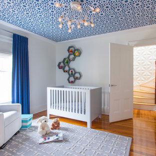 Exempel på ett mellanstort modernt babyrum, med vita väggar, mellanmörkt trägolv och orange golv