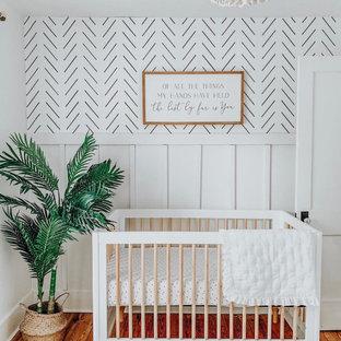 Diseño de habitación de bebé niño vintage, pequeña, con paredes blancas, suelo de madera en tonos medios y suelo marrón