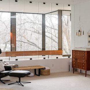 Cette image montre une très grand chambre de bébé neutre design avec un mur blanc et moquette.