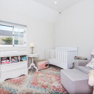 Modelo de habitación de bebé niña clásica, de tamaño medio, con paredes beige, suelo de madera clara y suelo marrón