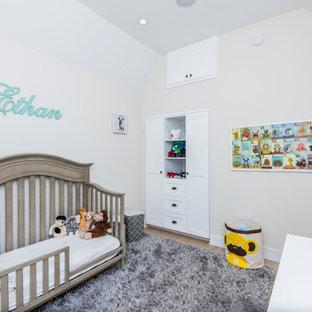 Exemple d'une chambre de bébé garçon chic de taille moyenne avec un mur beige, un sol en bois clair, un sol marron et un plafond voûté.