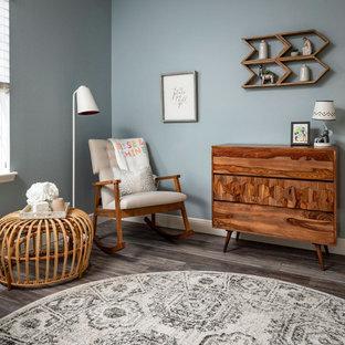 Modelo de habitación de bebé neutra vintage, pequeña, con paredes azules, suelo vinílico y suelo gris