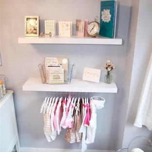 Diseño de habitación de bebé niña tradicional renovada, pequeña, con paredes púrpuras y moqueta