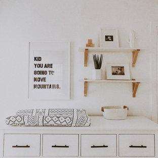 Idee per una cameretta per neonato moderna di medie dimensioni con pareti bianche, moquette e pavimento beige