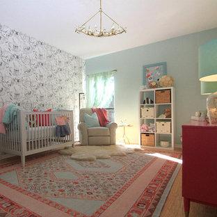 Aménagement d'une grand chambre de bébé fille éclectique avec un mur multicolore et un sol en bois brun.