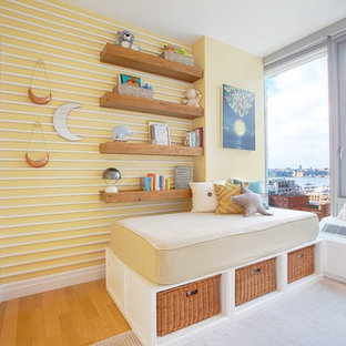 Photo of a small contemporary gender neutral nursery in New York with light hardwood flooring, grey walls and brown floors.