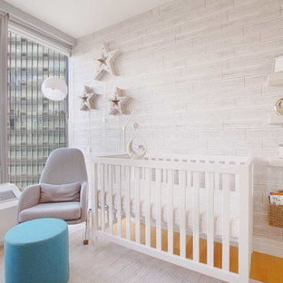 This is an example of a small contemporary gender neutral nursery in New York with grey walls, light hardwood flooring and brown floors.